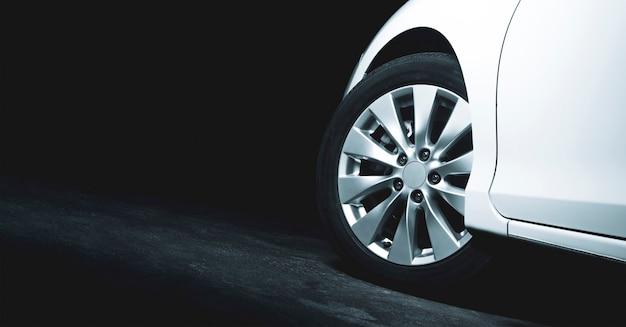 Aluminiowe felgi białego samochodu skręcają na cementową drogę parkingu z miejscem na kopię po lewej stronie