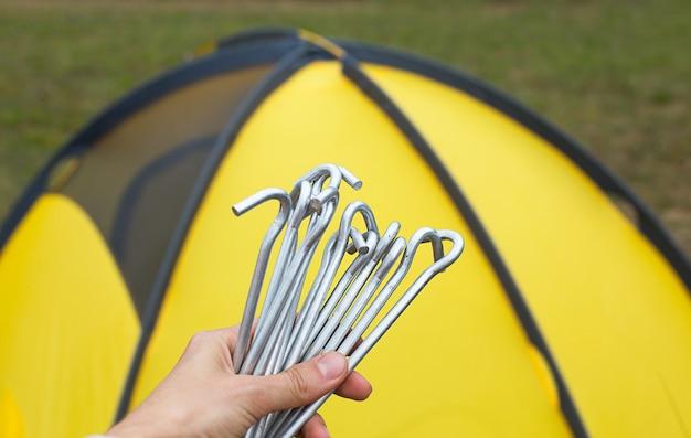 Aluminiowe kołki do montażu żółtego namiotu turystycznego w zbliżeniu ręki.