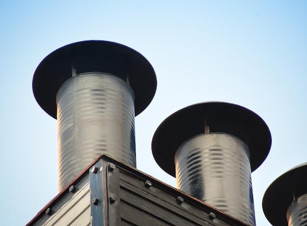 Aluminiowe kominy wentylacyjne instalowane na dachu fabryki.
