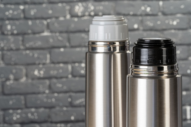 Aluminiowy metalowy termosu zbiornika butelka z bliska na stole