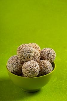 Amarantowy lub rajgira laddu, cholai ke laddo w zielonym pucharze na zielonym tle