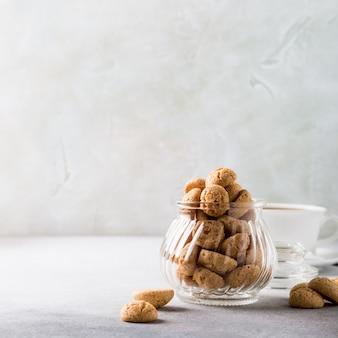Amaretti ciastka z białą filiżanką kawy