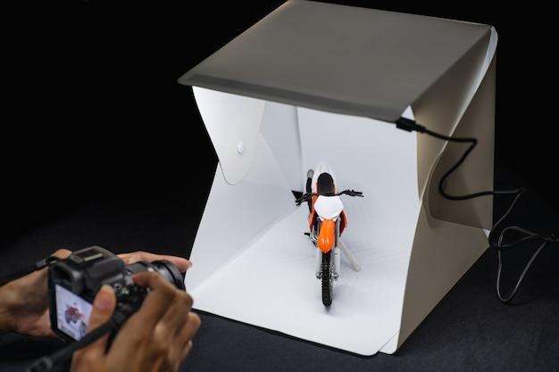 Amatorski fotograf pracujący nad lustrzanym aparatem fotograficznym