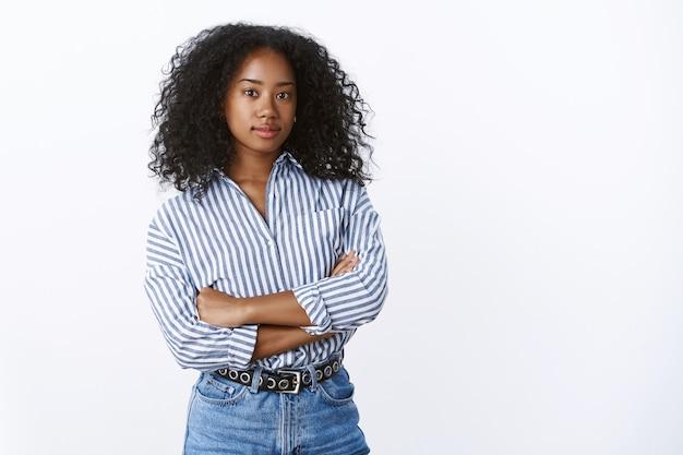 Ambitna, dobrze wyglądająca, inteligentna, kreatywna ciemnoskóra dziewczyna przedsiębiorca zdeterminowana, aby osiągnąć cel, stojąc pewnie ramiona skrzyżowane, patrząc na poważny, pewny siebie aparat, pozowanie białą ścianę