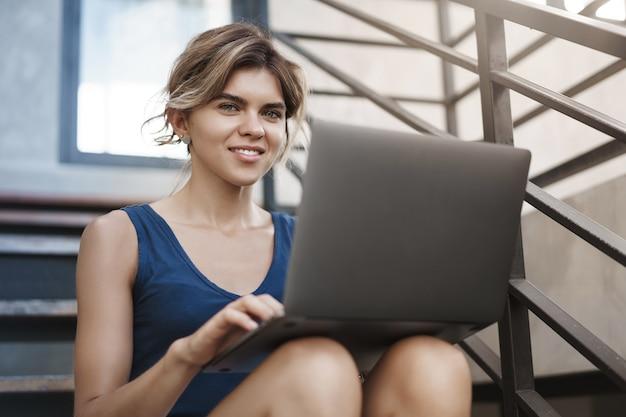 Ambitna, kreatywna młoda atrakcyjna blond dziewczyna siedzi na schodach na zewnątrz trzymając laptopa na kolanach uśmiechnięta zachwycona kamera ma świetny pomysł na ulepszenie kodu w programie, freelancing, cyfrowy proces pracy nomady.