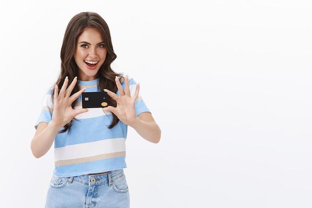 Ambitna, ładna młoda kobieta pokazuje znajomym nową czarną kartę kredytową, podekscytowana podróżami za granicę i płaceniem paypassem, ma dużo cashbacku za zakupy online, uśmiechając się radośnie robiąc zakupy w internecie