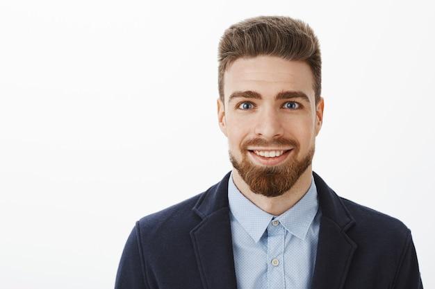 Ambitny przystojny i młody stylowy dojrzały mężczyzna z brodą i dużymi niebieskimi oczami uśmiechnięty podekscytowany i zadowolony z uśmiechem stojący w modnym garniturze na szarej ścianie, czekający na szansę pokazania umiejętności na szarej ścianie