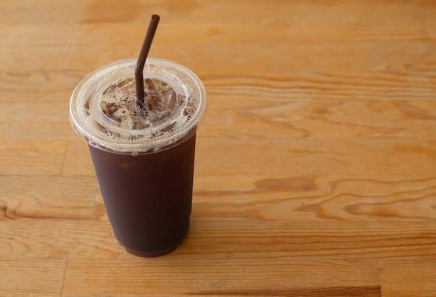 Americano lukrowa kawa w takeaway plastikowej filiżance na drewnianym biurku w kawa sklepie