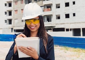 Amerykanin afrykańskiego pochodzenia dama w zbawczego hełma writing w notatniku blisko budynku w budowie