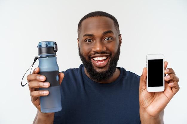 Amerykanin afrykańskiego pochodzenia atlety sporta mężczyzna mężczyzna z bieg sportami z telefonem komórkowym i wodą pitną od butelki.