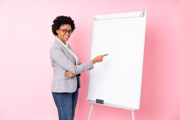 Amerykanin afrykańskiego pochodzenia biznesowa kobieta nad menchii ścianą