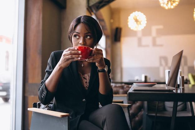 Amerykanin afrykańskiego pochodzenia biznesowa kobieta pije kawę w barze