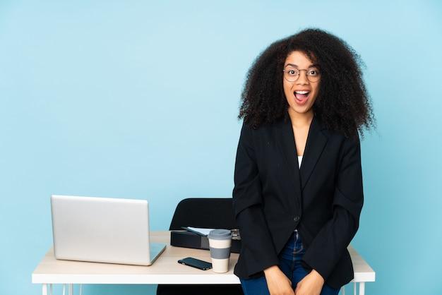 Amerykanin afrykańskiego pochodzenia biznesowa kobieta pracuje w jej miejscu pracy z niespodzianka wyrazem twarzy