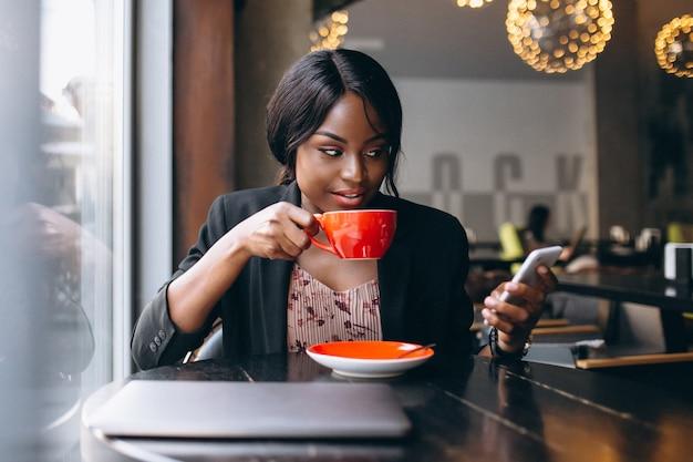 Amerykanin afrykańskiego pochodzenia biznesowa kobieta pracuje w kawiarni