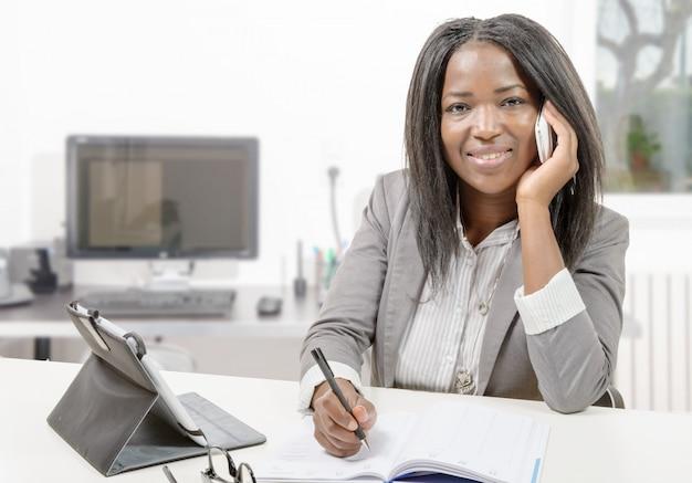 Amerykanin afrykańskiego pochodzenia biznesowa kobieta pracuje z pastylką