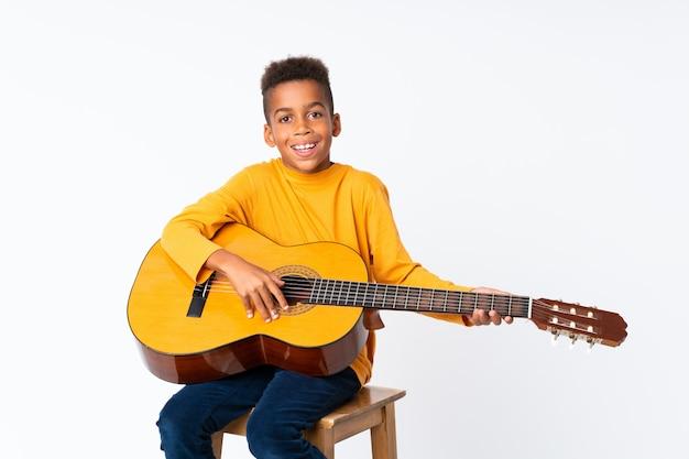 Amerykanin afrykańskiego pochodzenia chłopiec z gitarą nad odosobnionym bielem