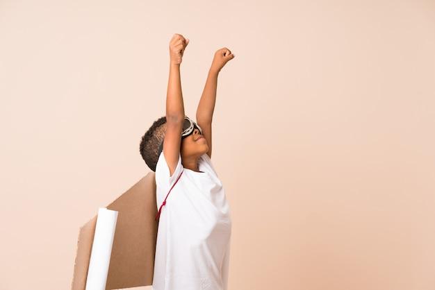 Amerykanin afrykańskiego pochodzenia chłopiec z lotnika kapeluszem i skrzydłami nad odosobnionym