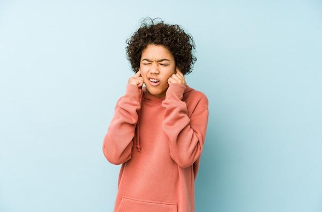 Amerykanin afrykańskiego pochodzenia chłopiec zakrywający ucho z rękami.