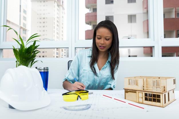 Amerykanin afrykańskiego pochodzenia dama na krześle bierze notatki blisko zbawczego hełma i modela dom na stole