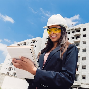 Amerykanin afrykańskiego pochodzenia dama w zbawczym hełmie z notatnikiem blisko budynku w budowie