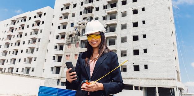 Amerykanin afrykańskiego pochodzenia dama w zbawczym hełmie z smartphone i pomiarową taśmą blisko budynku w budowie