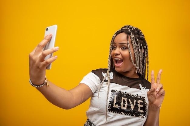 Amerykanin afrykańskiego pochodzenia dziewczyna bierze selfie fotografie z jej telefonem komórkowym na kolorze żółtym