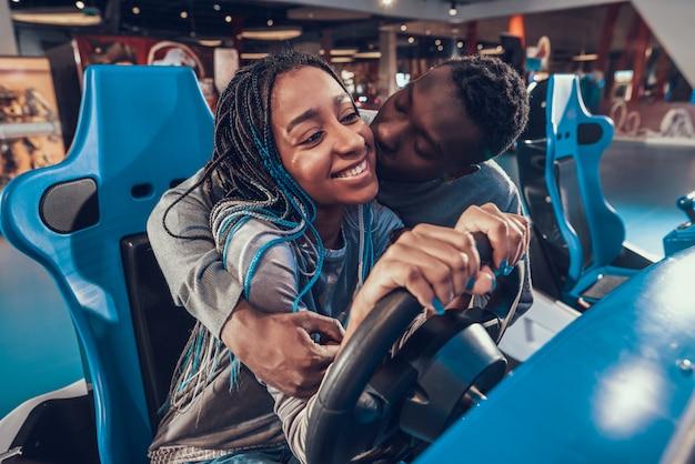 Amerykanin afrykańskiego pochodzenia dziewczyna jedzie błękitnego samochód w arkadzie.