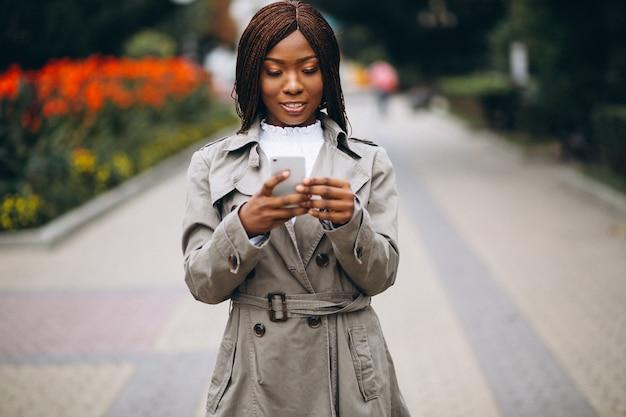 Amerykanin afrykańskiego pochodzenia i caucasian kobiety używa telefon