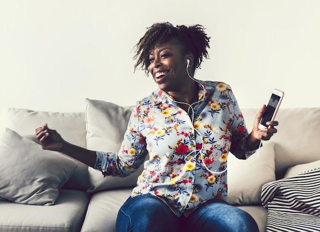 Amerykanin afrykańskiego pochodzenia kobieta cieszy się muzykę w domu