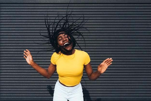 Amerykanin afrykańskiego pochodzenia kobieta macha jej dreadlocks