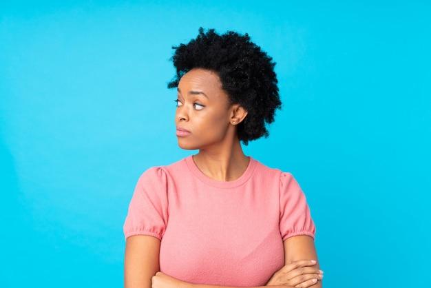 Amerykanin afrykańskiego pochodzenia kobieta nad błękit ścianą