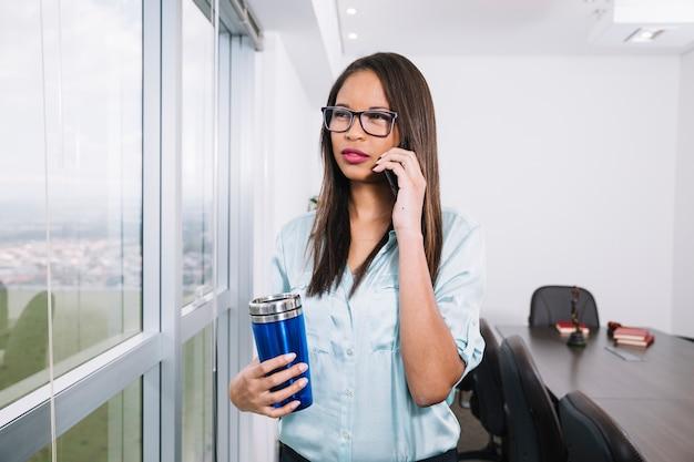 Amerykanin afrykańskiego pochodzenia kobieta opowiada na smartphone blisko okno w biurze z termosem