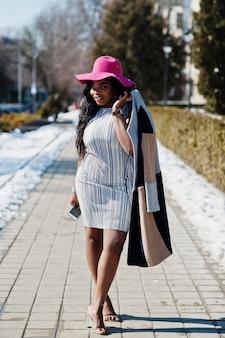 Amerykanin afrykańskiego pochodzenia kobieta przy kapeluszem i żakietem z telefonu odprowadzeniem przy ulicami.