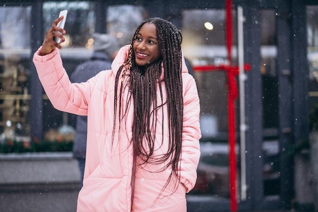 Amerykanin afrykańskiego pochodzenia kobieta robi selfie na telefonie