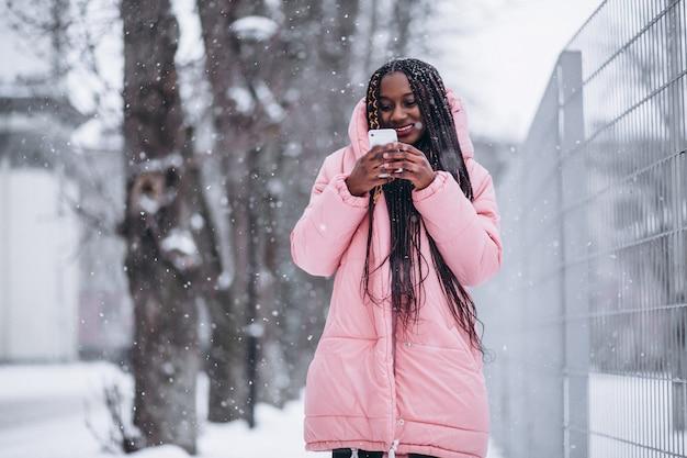 Amerykanin afrykańskiego pochodzenia kobieta używa telefon