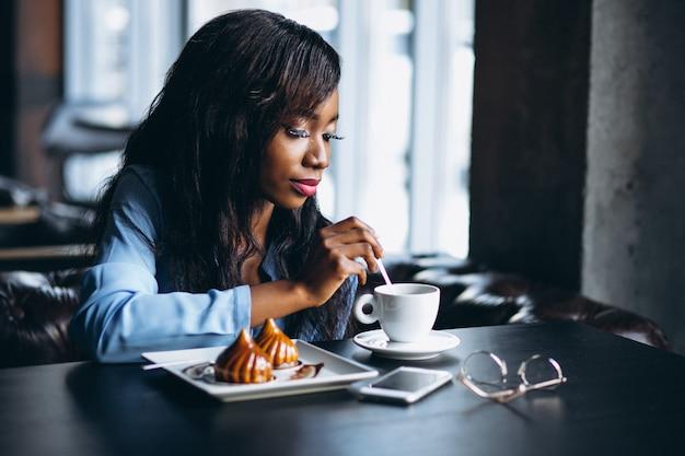 Amerykanin afrykańskiego pochodzenia kobieta w cukiernianym łasowanie deserze