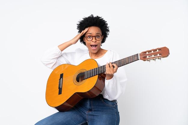 Amerykanin afrykańskiego pochodzenia kobieta z gitarą nad odosobnioną biel ścianą