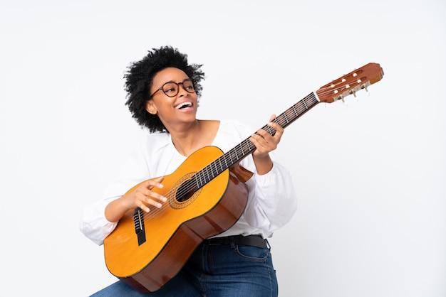 Amerykanin afrykańskiego pochodzenia kobieta z gitarą nad odosobnionym