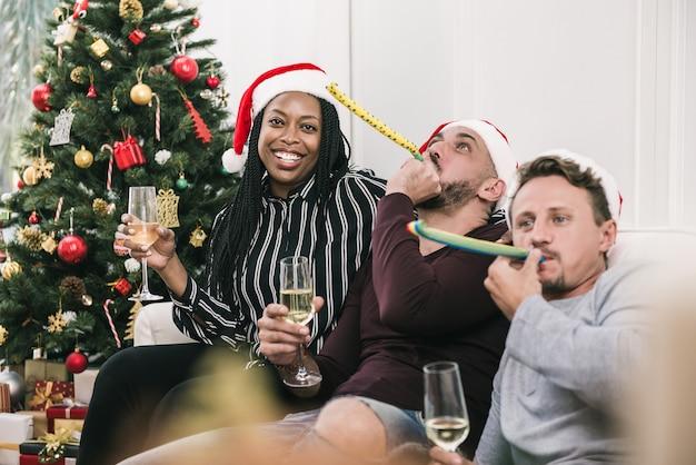 Amerykanin afrykańskiego pochodzenia kobieta z grupą przyjaciele świętuje boże narodzenia w domu