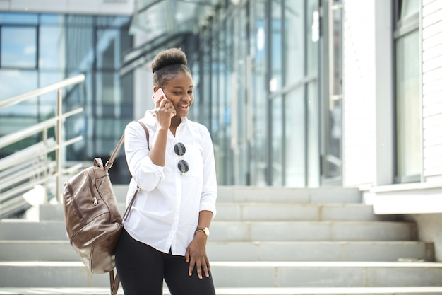 Amerykanin afrykańskiego pochodzenia kobieta z plecaka chodzić plenerowy i opowiadać na telefonie komórkowym
