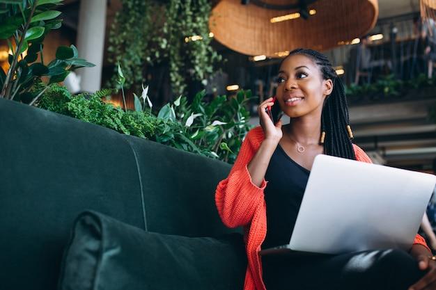 Amerykanin afrykańskiego pochodzenia kobieta z telefonem i laptopem w kawiarni