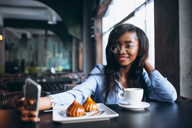 Amerykanin afrykańskiego pochodzenia kobieta z telefonem w kawiarni