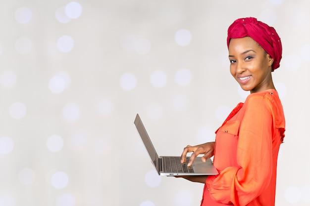 Amerykanin afrykańskiego pochodzenia kobiety mienia laptop