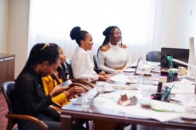Amerykanin afrykańskiego pochodzenia koledzy, załoga różnorodności żeńscy partnerzy w biurze siedzą przy stole.