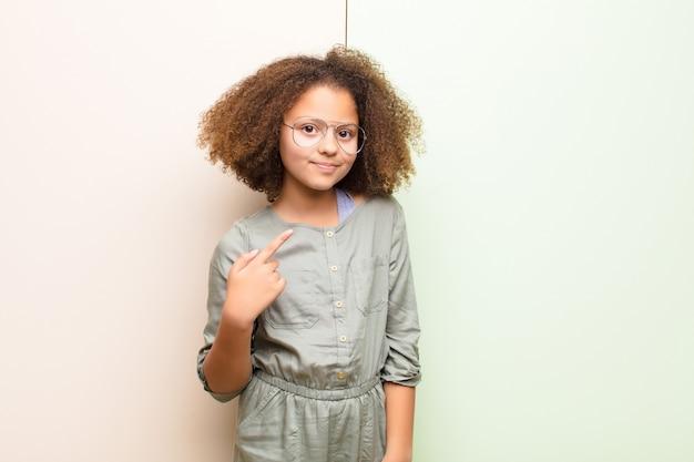 Amerykanin afrykańskiego pochodzenia mała dziewczynka patrzeje dumny, ufny i szczęśliwy, ono uśmiecha się i wskazuje jaźń lub robi numerowi jeden znakowi przeciw płaskiej ścianie