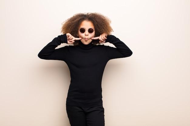 Amerykanin afrykańskiego pochodzenia mała dziewczynka przeciw płaskiej ścianie. fajna koncepcja