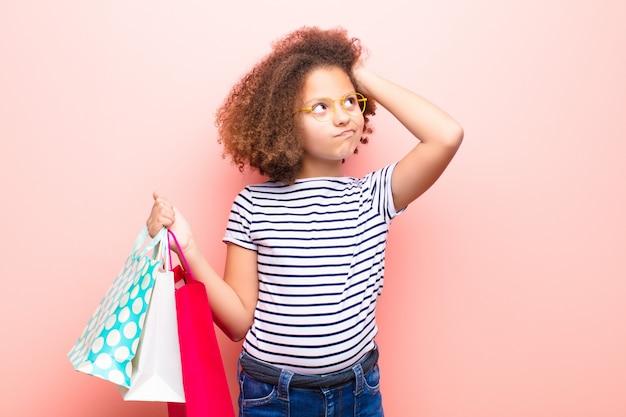 Amerykanin afrykańskiego pochodzenia mała dziewczynka przeciw płaskiej ścianie z torba na zakupy