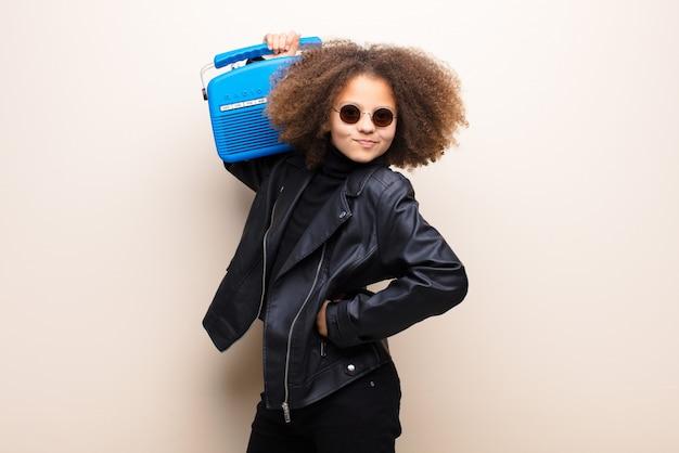 Amerykanin afrykańskiego pochodzenia mała dziewczynka przeciw płaskiej ściany słuchającej muzyce z oldfashioned radiem