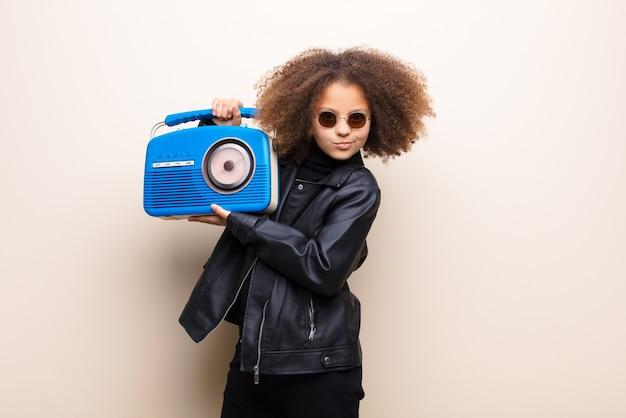 Amerykanin afrykańskiego pochodzenia mała dziewczynka słucha muzyka z oldfashioned radiem