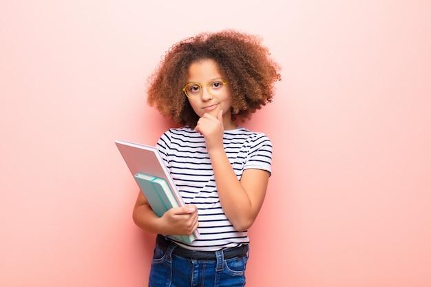 Amerykanin afrykańskiego pochodzenia mała dziewczynka trzyma książkę przeciw płaskiej ścianie